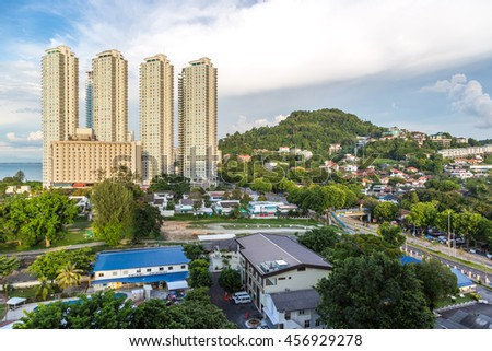 Penang, Malaysia - June 22nd 2016 - Houses in the middle of tropical forest in a blue sky day in Penang city in Malaysia.