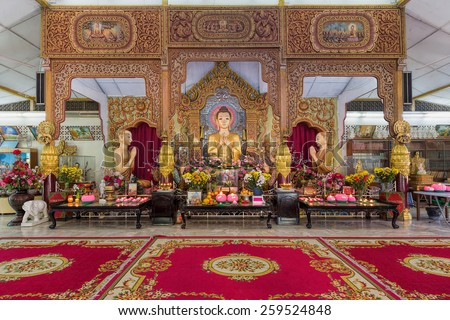 PENANG, MALAYSIA, MARCH 10, 2015: Dhammikarama Burmese Buddhist Temple Altar with Buddha and two Monks Statues. This temple is a popular tourist attraction for both locals and tourists. - stock photo
