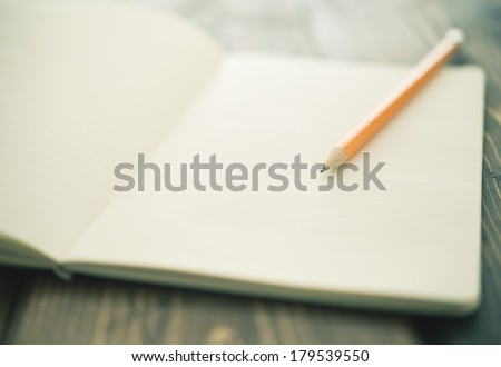 Pencil and a blank notebook up close