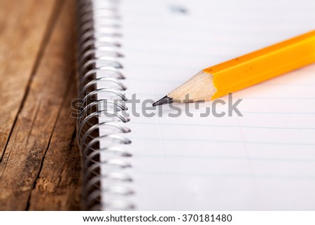 Pencil and a notebook up close - stock photo