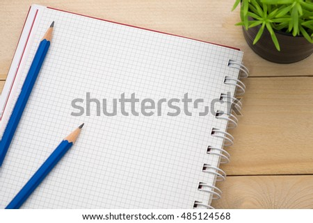 pencil and diary notebook on wooden desk