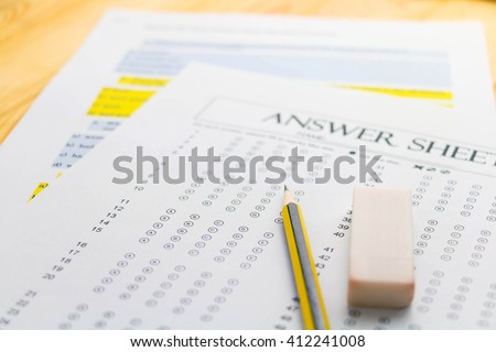 pencil and eraser on answer sheet - stock photo