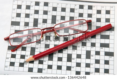 Pencil and glasses on the newspaper with a crossword. - stock photo