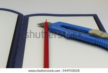pencil and Knife Sharpener on Note book  isolated on white background - stock photo