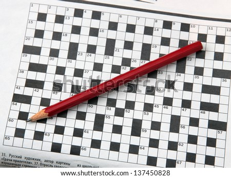 Pencil and newspaper with a crossword. - stock photo