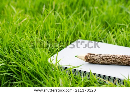 Pencil and notebook on grass - stock photo