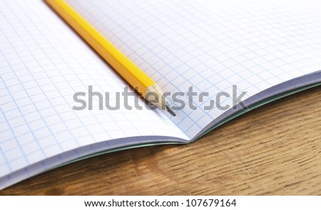 pencil and notebook on wood - stock photo