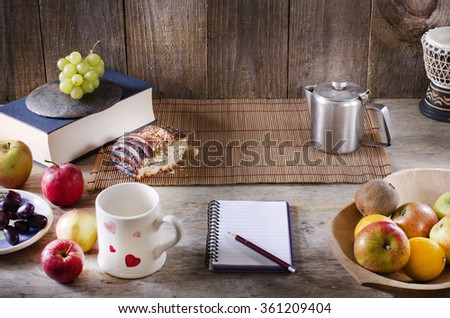 Pencil and notebook with copy space on wooden table. Healthy breakfast concept. Fruits and drink. - stock photo