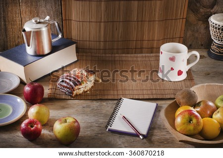 Pencil and notebook with copy space on wooden table. Healthy breakfast concept. Fruits, drink, sweet bun. - stock photo