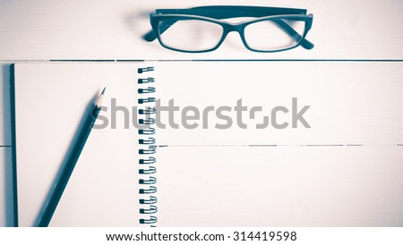 pencil and notepad with eyeglasses over white table view from above vintage style