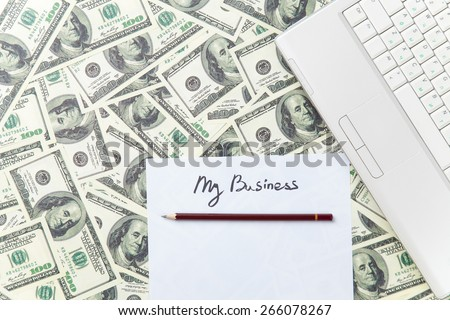 pencil and paper with My Business words near notebook on dollars background