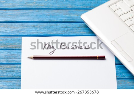 pencil and paper with My Business words near notebook on wooden background