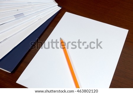 Pencil and paperwork with reports arranged on wooden table