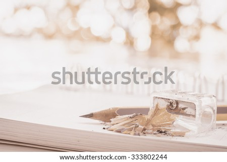 Pencil and pencil sharpener on note book - stock photo