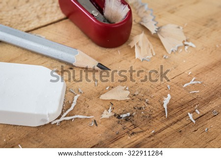 Pencil and rubber eraser on wooden table - stock photo