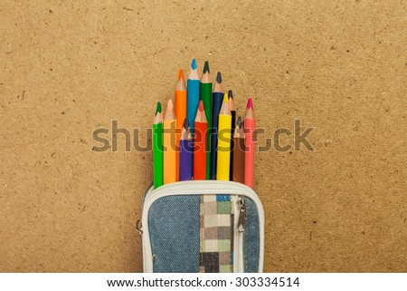 Pencil-case with colorful pencils on cork background - stock photo