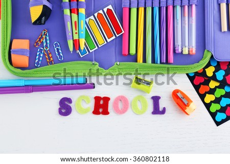 Pencil case with various stationery on wooden table
