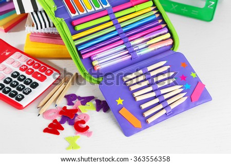 Pencil case with various stationery on wooden table, close up - stock photo