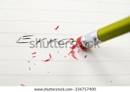 Pencil closeup erasing an error on paper - stock photo