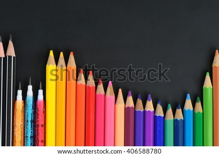 Pencil crayons on black background - stock photo