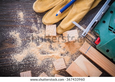 Pencil electric jigsaw sawdust leather protective gloves and wooden studs on vintage wood background construction concept.
