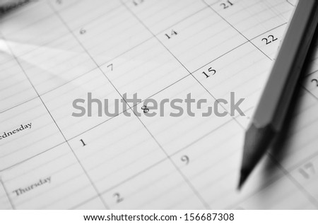 Pencil lying on a calendar showing different dates and days conceptual of schedules, time management, events, deadlines and organisation - stock photo