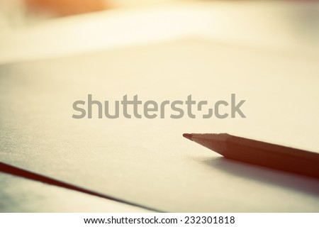Pencil lying on blank piece of paper in morning light. Creative work, writing, drawing etc. Vintage natural mood - stock photo