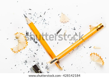 Pencil, metal sharpener and pencil shavings on white background. Horizontal image.