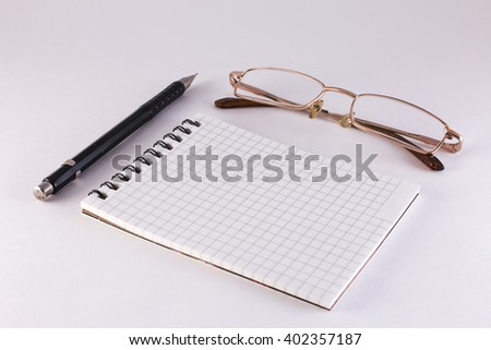 pencil notebook and glasses on a white background