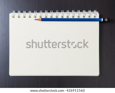 Pencil on a blank note book. Sketch book blank page. Writing a diary book. Blank paper binder. Copy space on blank book. Binding book space for text. Student Book. Office book top view.  - stock photo