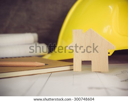 Pencil on architectural blueprint of office building over blurred Safety yellow hat and blueprint