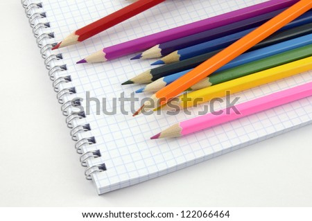 pencil on checked school paper of notepad - stock photo