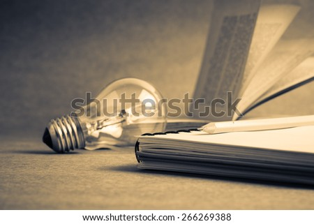 Pencil on notebook with light bulb and old book - stock photo