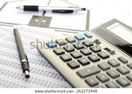 pencil, pen and calculator on plans and sheet number - stock photo