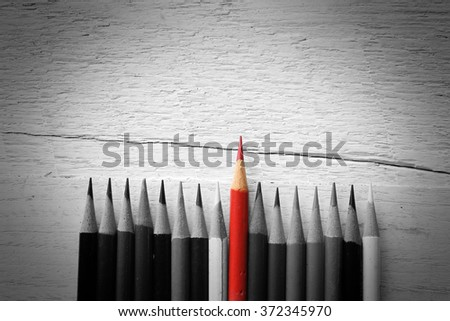 Pencil, red pencil in the middle space between black and white, conceptual differences. - stock photo