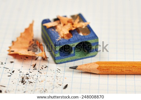 pencil, sharpener and pencil residues and mine on a squared paper - stock photo