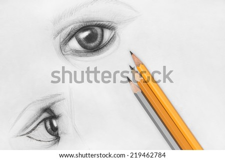 Pencil sketch of female eyes on white paper with pencils - stock photo
