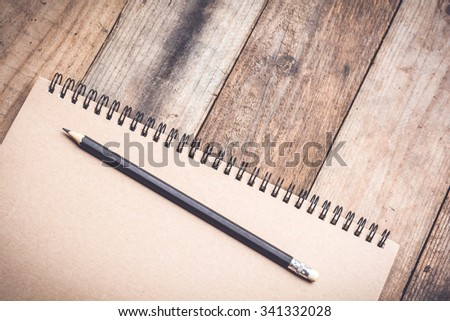 Pencil with notebook placed on a old wooden