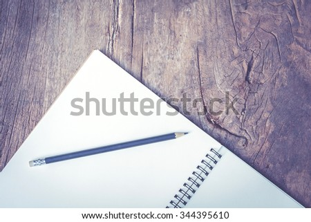 Pencil with notebook placed on a old wooden table - stock photo