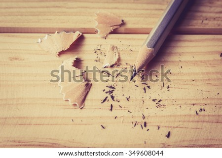 Pencil with sharpening shavings on wooden table - stock photo