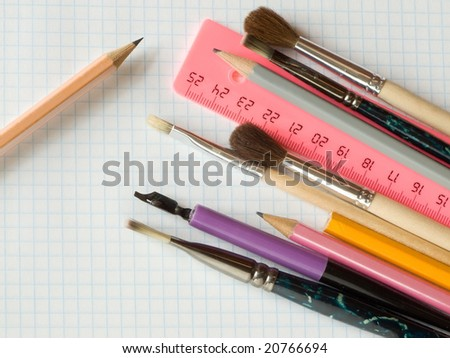 pencils and brushes on squared sheet of a copybook