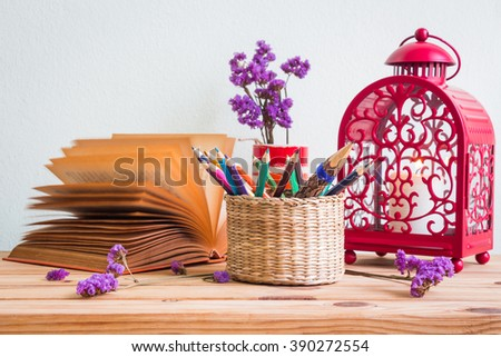 Pencils and colored pencils in the basket, open book, purple flowers in a white vase and red lantern on a wooden table, selective focus - stock photo