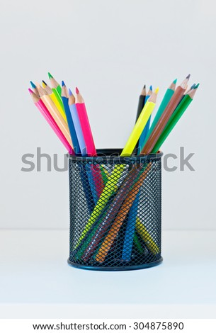 Pencils in a case on the light-coloured shelf with copy-space - stock photo