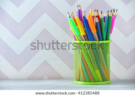 Pencils in metal holder on colour background