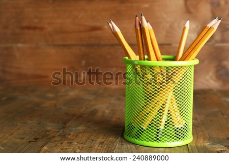Pencils in metal holder on rustic wooden background - stock photo