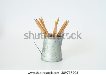 Pencils in small vase zinc on white background