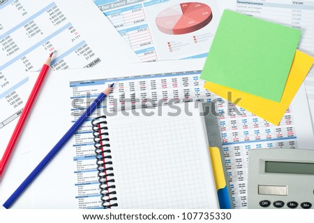 pencils notebook and notes over financial documents