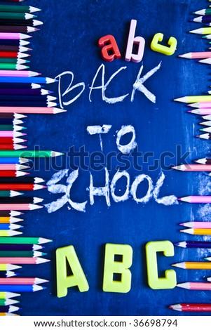 Pencils on blackboard in a classroom - stock photo