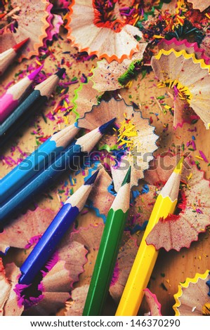 Pencils on wooden table with sawdust particles - stock photo