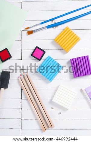 pencils, painting brushes, plasticine blocks and ink pads on white wood - stock photo